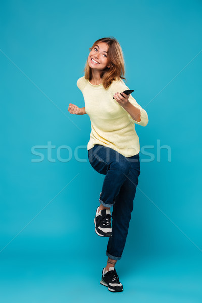 Full length image of cheerful woman in sweater rejoice Stock photo © deandrobot