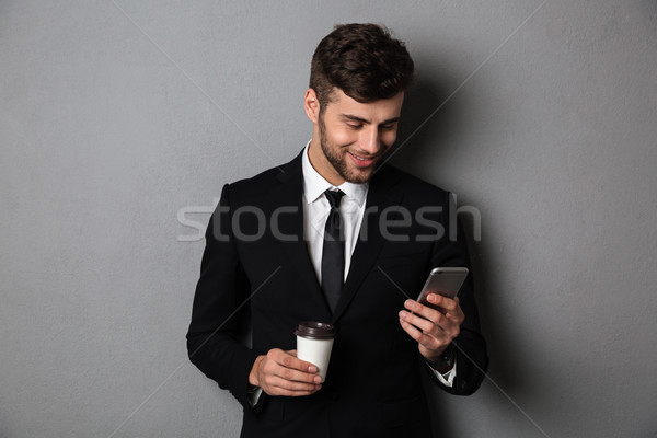 Young handsom man in formal wear checking news on smartphone whi Stock photo © deandrobot