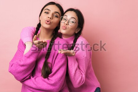 Two satisfied young woman with closed eyes holding gift box betw Stock photo © deandrobot