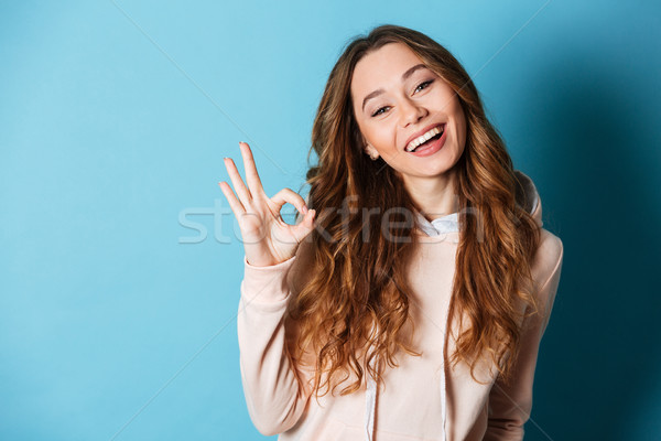 Cute smiling woman showing okay gesture. Stock photo © deandrobot