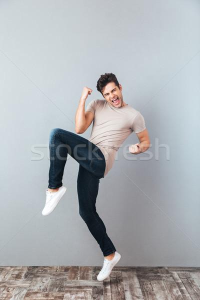 Full length portrait of a happy cheery man celebrating Stock photo © deandrobot
