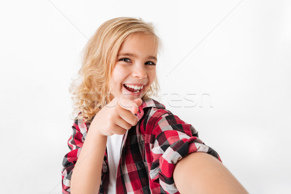 Portrait of a cheery little girl pointing finger at camera Stock photo © deandrobot