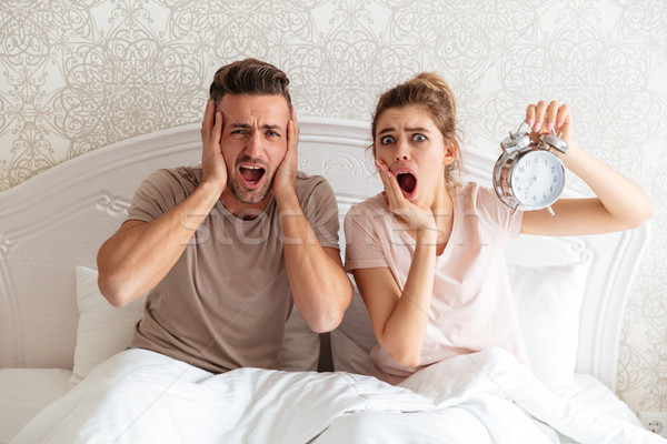 Shocked Lovely couple sitting together on bed with alarm clock Stock photo © deandrobot