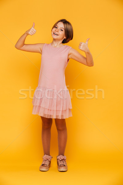 Portrait of happy carefree girl smiling and showing thumbs up isolated Stock photo © deandrobot
