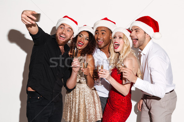 Portrait of a smiling young multiracial group of friends celebrating Stock photo © deandrobot