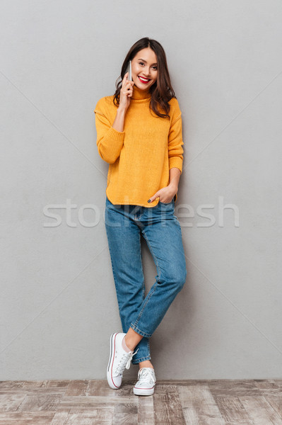 Full length image of Pleased brunette woman in sweater Stock photo © deandrobot