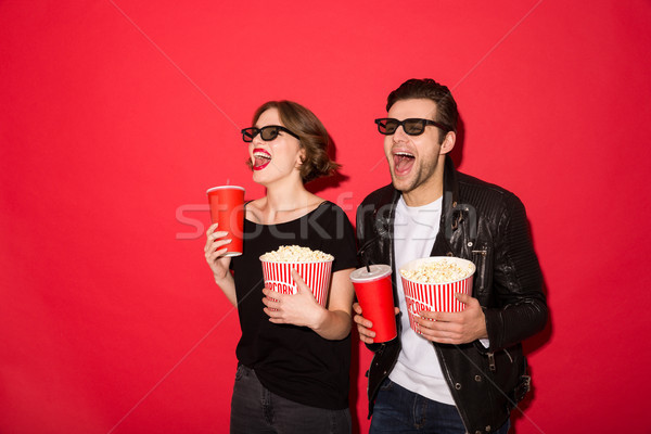 Happy punk couple in eyeglasses holding soda and popcorn Stock photo © deandrobot