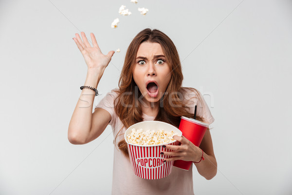 Portrait of a shocked pretty girl holding plastic cup Stock photo © deandrobot