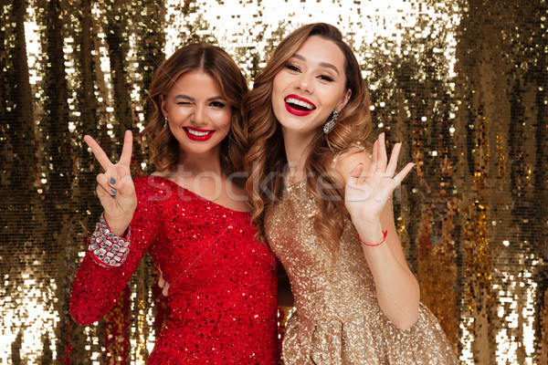Portrait of two cheerful smiling women in sparkly dresses Stock photo © deandrobot