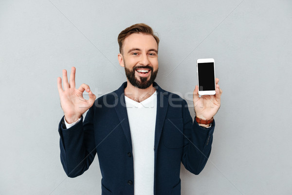 Happy bearded man in business clothes showing blank smartphone screen Stock photo © deandrobot
