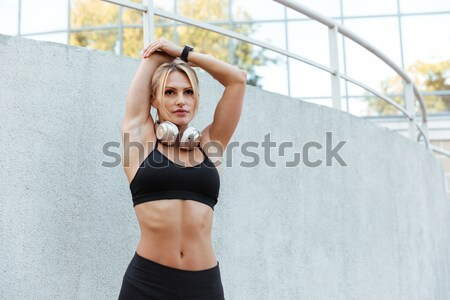Sensual fitness woman warming up in studio and looking away Stock photo © deandrobot