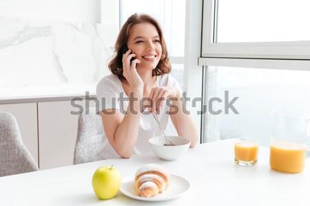 Cheerful brunette girl in white tshirt talking on mobile phone w Stock photo © deandrobot