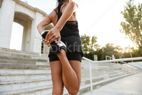 Back view of a fitness woman in earphones stretching Stock photo © deandrobot
