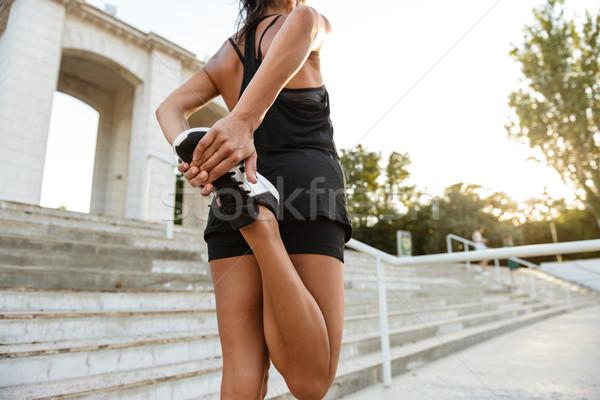 Hátulnézet fitnessz nő fülhallgató nyújtás lábak lépcsősor Stock fotó © deandrobot