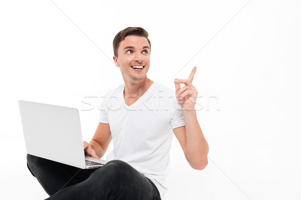 Portrait of a cheery handsome man holding laptop computer Stock photo © deandrobot