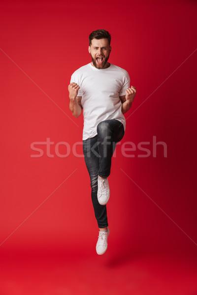 Jóképű fiatalember ugrik mutat nyertes kézmozdulat Stock fotó © deandrobot