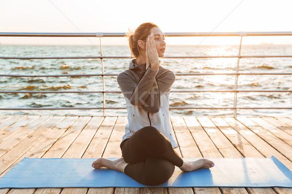 Csinos fiatal lány ül jóga pozició fitnessz Stock fotó © deandrobot