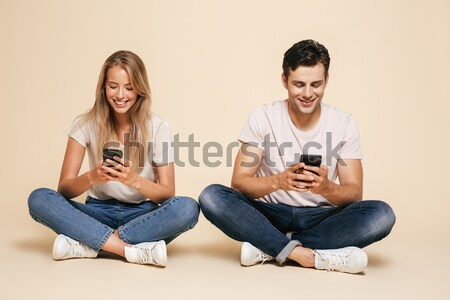 Image of optimistic friends man and woman 20s in denim clothing  Stock photo © deandrobot