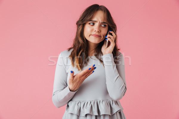 Portret verward jong meisje praten mobiele telefoon geïsoleerd Stockfoto © deandrobot