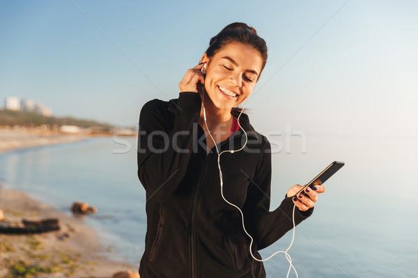 満足した 小さな スポーツウーマン 音楽を聴く イヤホン 携帯電話 ストックフォト © deandrobot