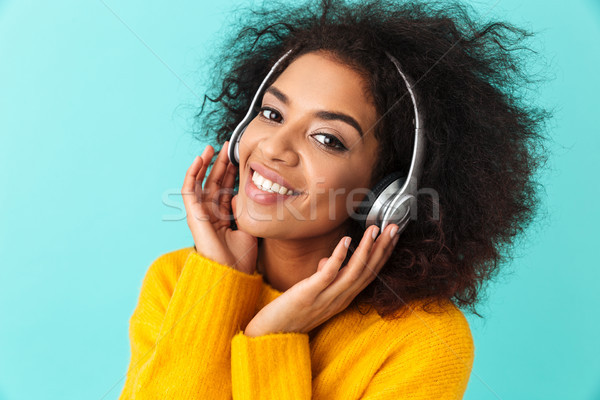 African american smiling woman in yellow shirt listening to musi Stock photo © deandrobot