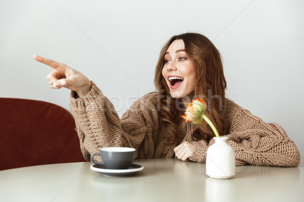 Photo of attractive woman resting in cozy cafe, and pointing fin Stock photo © deandrobot