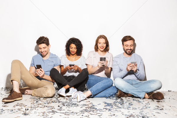 Group of happy multiracial people sitting on a floor Stock photo © deandrobot