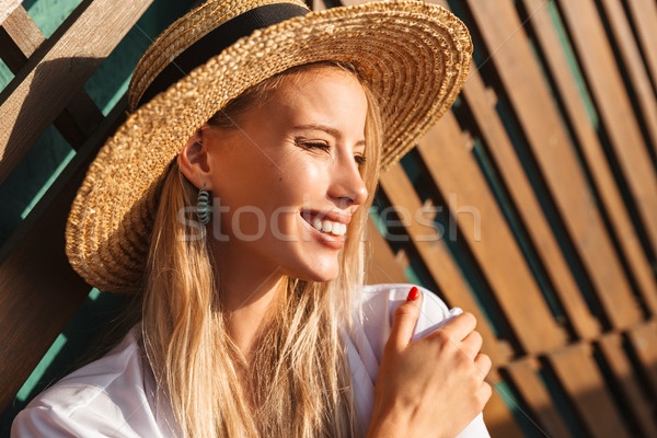 Portrait of happy cute blond woman 20s in straw hat and swimwear Stock photo © deandrobot