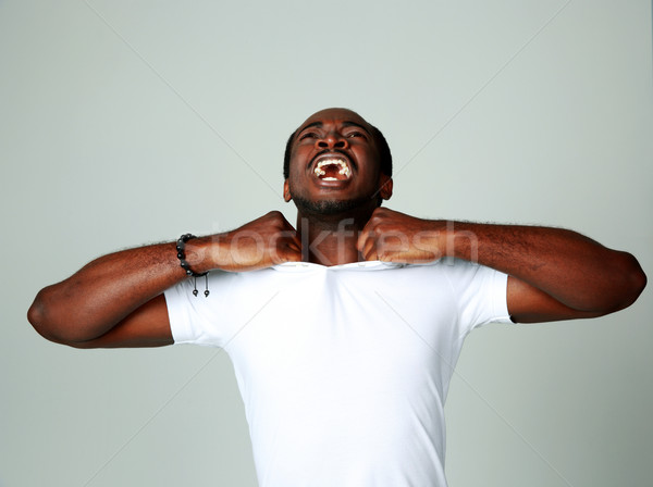 Angry african man screaming on gray background Stock photo © deandrobot