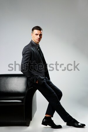 Confident businessman leaning at sofa on a gray background Stock photo © deandrobot