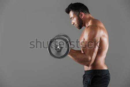 Portrait of muscular man lifting dumbbell over white background Stock photo © deandrobot