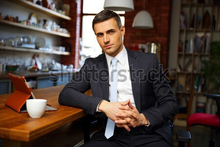 Confident businessman in formal cloths drinking coffee and reading news in the kitchen Stock photo © deandrobot