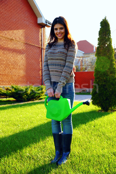 Smiling woman standing with watering pot in garden Stock photo © deandrobot