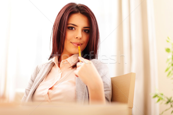 Portrait of a young beautiful confident woman in casual business cloths holding a pencil Stock photo © deandrobot