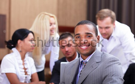 Multi ethnic business team at a meeting. Interacting. Focus on woman Stock photo © deandrobot