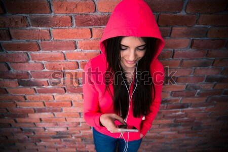 Happy woman using smartphone over brick wall Stock photo © deandrobot