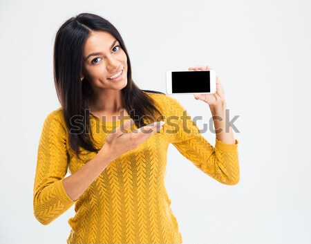 Cute woman pointing finger on smartphone screen Stock photo © deandrobot
