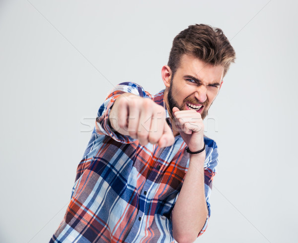 Angry young man hitting at camera Stock photo © deandrobot