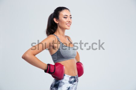 Smiling sports woman standing in boxing gloves  Stock photo © deandrobot