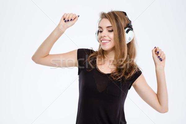 Smiling woman listening music in headphones Stock photo © deandrobot