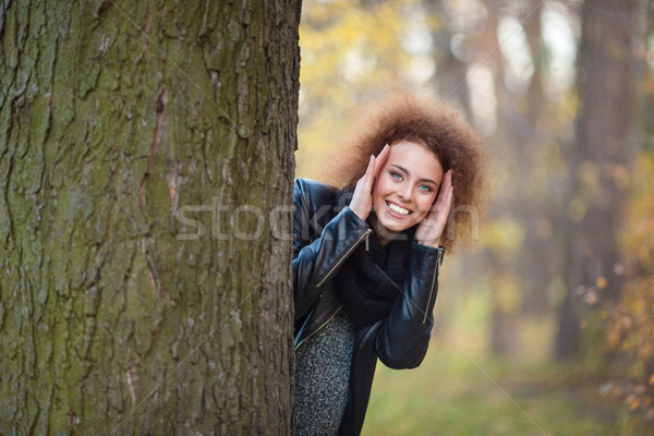 Glimlachende vrouw uit achter boom portret krulhaar Stockfoto © deandrobot