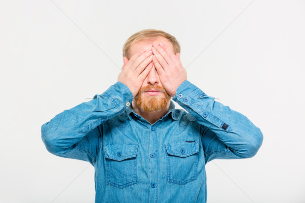 Stock photo: Young handsome blond bearded male with eyes covered by hands