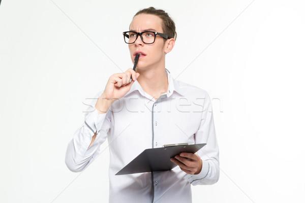 Pensive man holding clipboard Stock photo © deandrobot