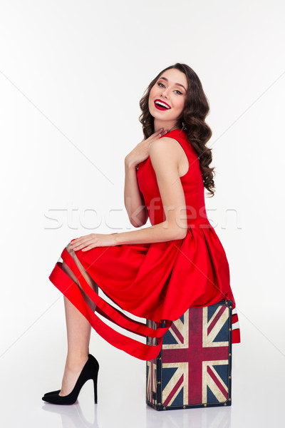 Charming happy woman posing on vintage suitcase with british flag Stock photo © deandrobot