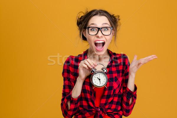 Szórakoztató csinos fiatal nő tart ébresztőóra kiált Stock fotó © deandrobot