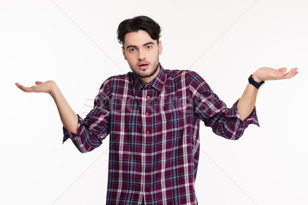 Portrait of a young man shrugging shoulders  Stock photo © deandrobot