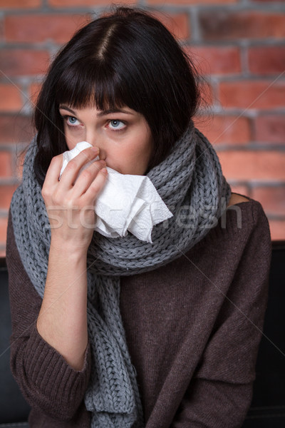 Young sick woman sitting in scarf and sweater with handkerchief Stock photo © deandrobot