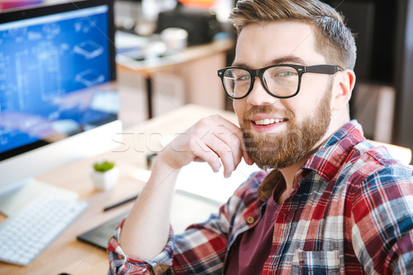 Happy attractive man working and designing project on computer  Stock photo © deandrobot