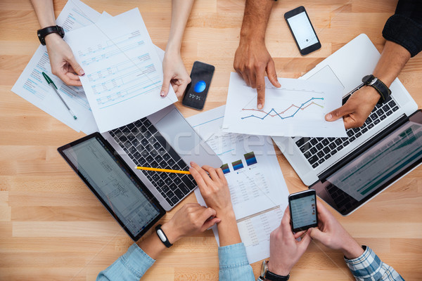 Team working for financial report using laptops and smartphones Stock photo © deandrobot