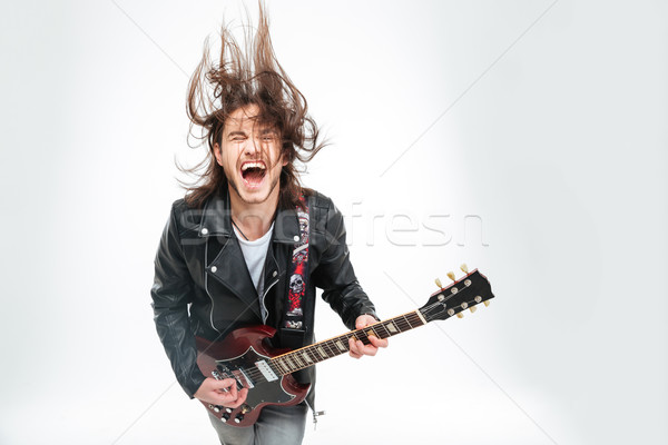 Excited young man with electric guitar shouting and shaking head Stock photo © deandrobot